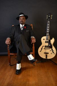 Nick Colionne in chair next to his Epiphome guitar